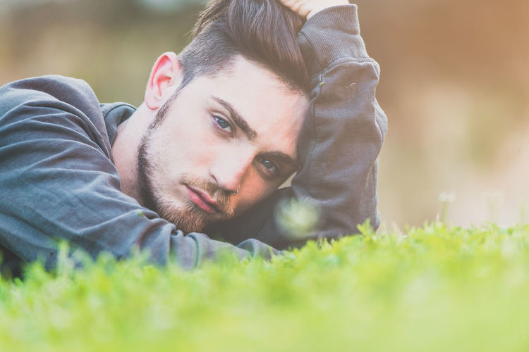 Portrait Of Young Man Lying Down On Field