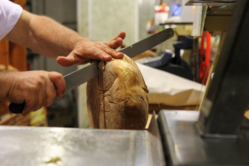 Cropped Image Of Chef Cutting Bread In Kitchen