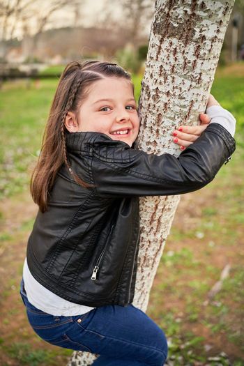 Portrait of smiling girl on tree trunk