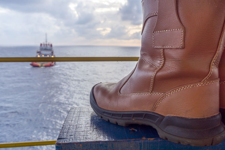 safety shoe Oil Field Construction Anchor Handling Tug Site Rest Cloudy Morning Ocean Wave Bench Handrail  Tugboat Tug Boat Boat Ship Vessel Offshore Offshore Life Industry Safety Low Section Water Nautical Vessel Sea Sunset Human Leg Shoe Close-up Sky Horizon Over Water