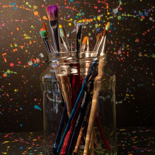 Close-up of paintbrushes in jar on table