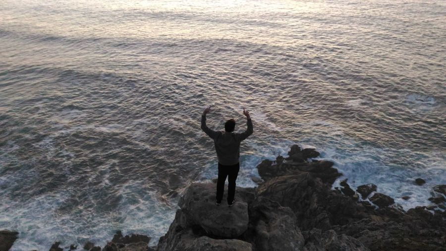 High angle view of man with arms raised standing at rocky beach