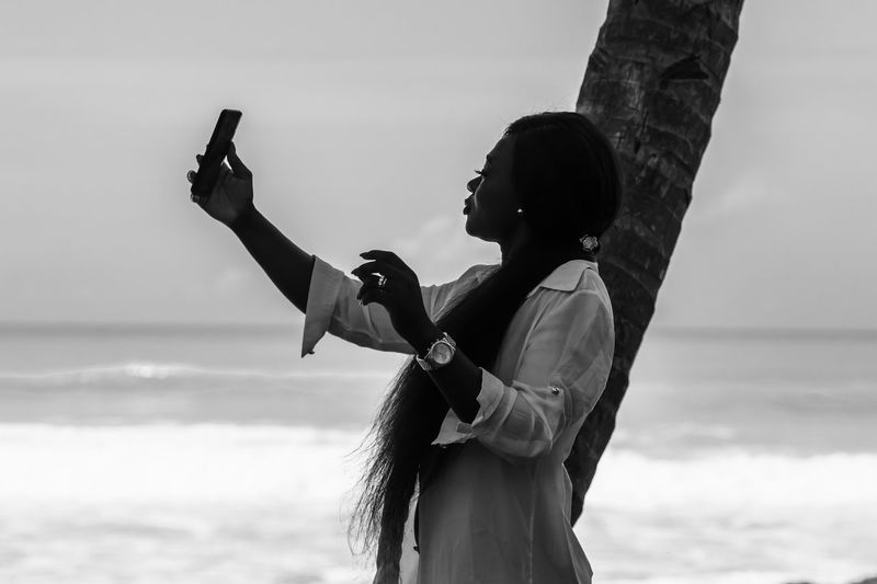 Africa woman from ghana is standing by phone in hand by the sea in axim ghana.