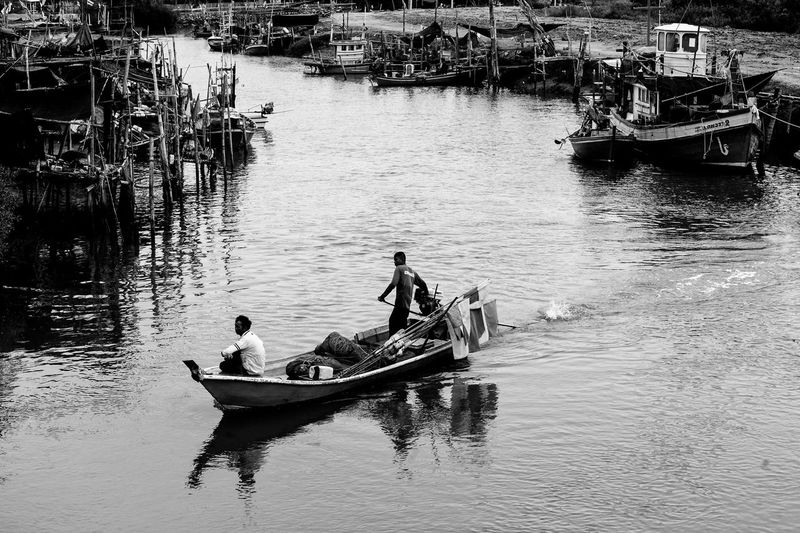 People sitting on boat in lake