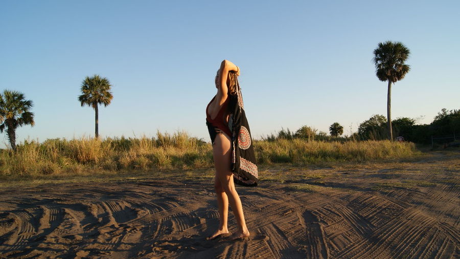 Side view full length of young woman wearing one piece swimsuit holding scarf on sand