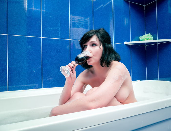 Naked woman drinking wine while sitting in bathtub
