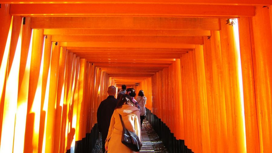 Rear View Of People Walking On Street With Torii Gate For Fushimi Inari Shrine