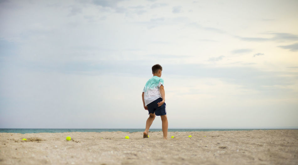 Rear view of man on beach against sky