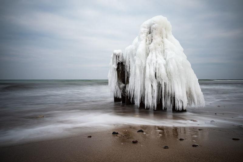 Frozen wooden posts on beach against sky
