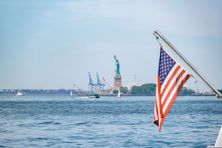 Lady Liberty still stands tall! Sky Flag Water Architecture Patriotism Waterfront Built Structure Nature Transportation Nautical Vessel Building Exterior Day No People Travel Travel Destinations City Freedom Outdoors Independence Monument