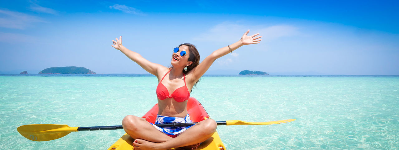 Happy Woman With Arms Raised Sitting On Kayak In Sea