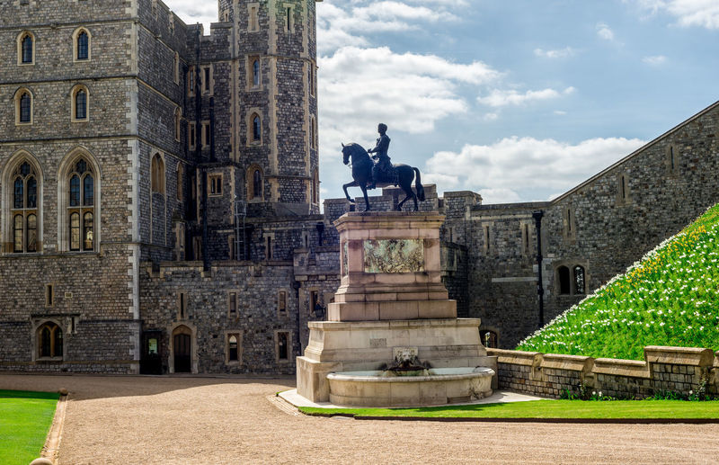 A bronze statue of Charles II on horseback next to the South Wing entrance in Windsor Castle, England Berkshire Bronze Great Britain Her Majesty London Monarchy Official Square Statue The Queen Tourist Attraction  United Kingdom Wing England Fortress Horseback Residence Ride Royal Summer Travel Destinations Upper Visit Windsor Castle