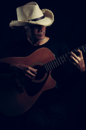 Acoustic guitar man Musical Instrument Guitar String Instrument Hat Music Arts Culture And Entertainment Musical Equipment One Person Musician Playing Artist Men Plucking An Instrument Clothing Real People Holding Acoustic Guitar String Musical Instrument String Guitarist Dark Black Background Senirupa Hat Countryside
