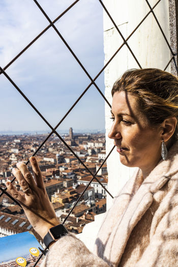 Woman looking through window in city