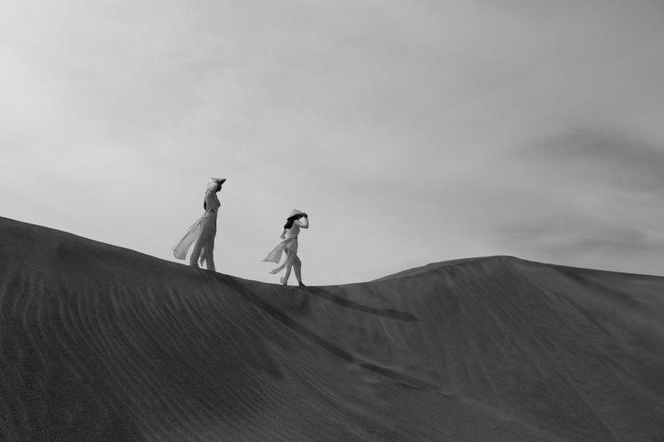 Women On Sand Dune In Desert Against Sky