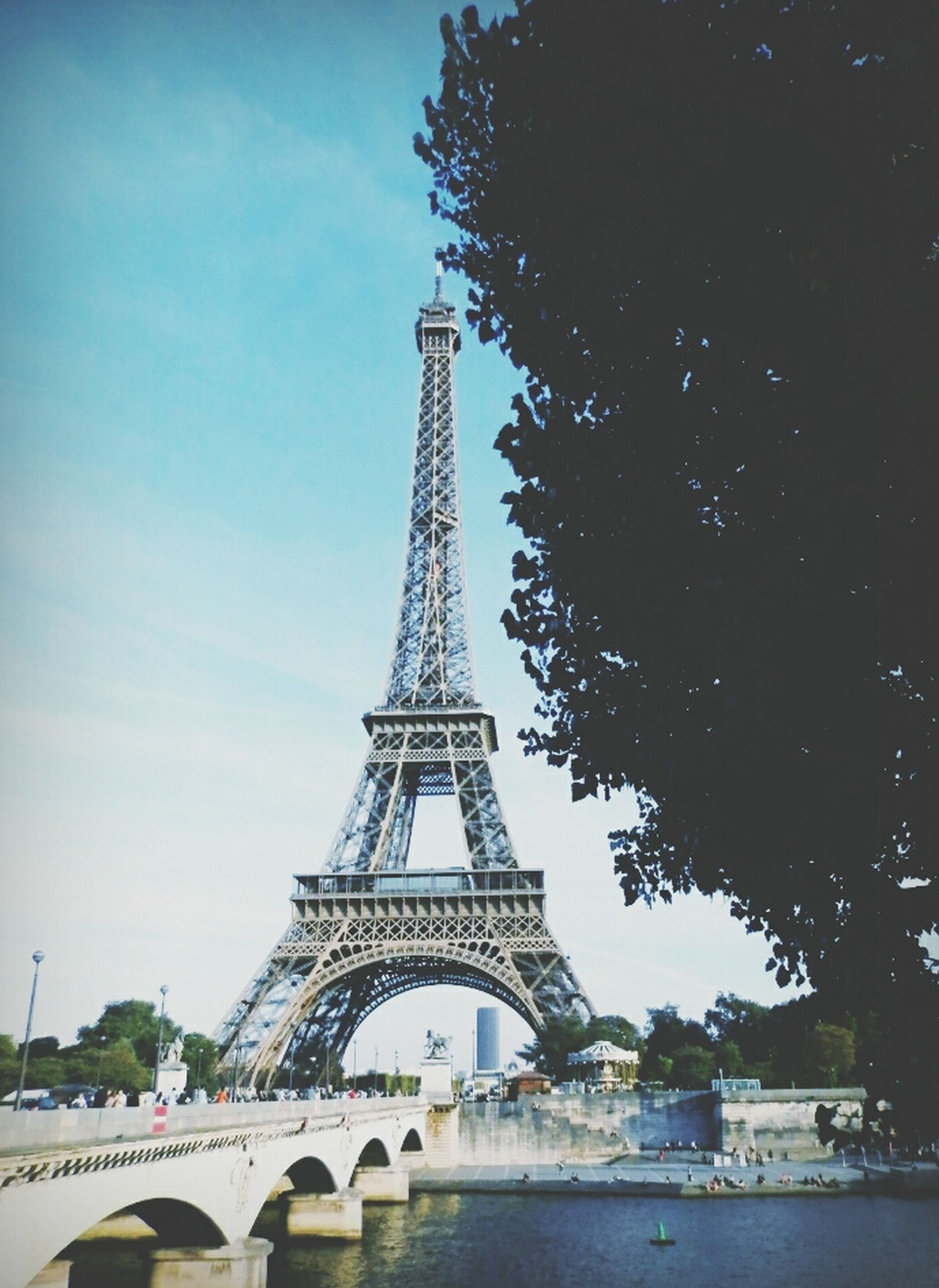 architecture, built structure, eiffel tower, famous place, travel destinations, sky, tower, transportation, international landmark, bridge - man made structure, connection, travel, capital cities, tourism, engineering, tall - high, metal, tree, culture, city