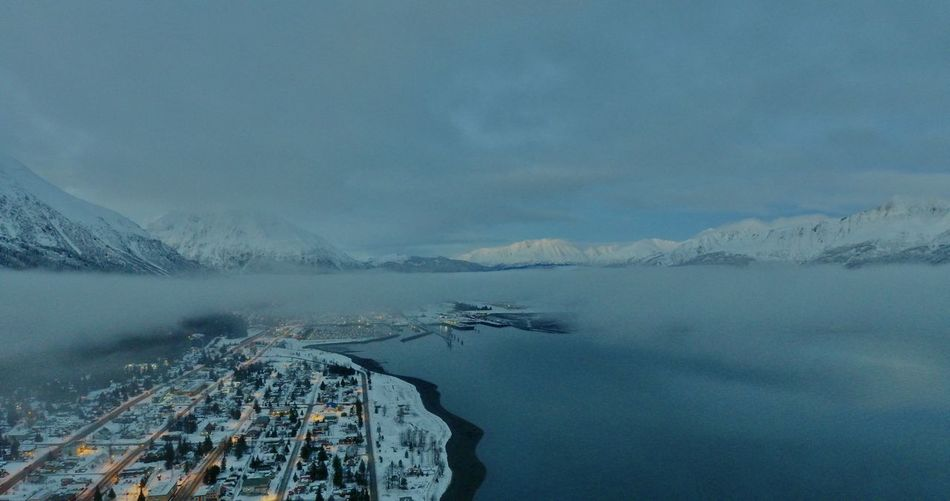 Aerial view of lake by snowcapped mountains against sky