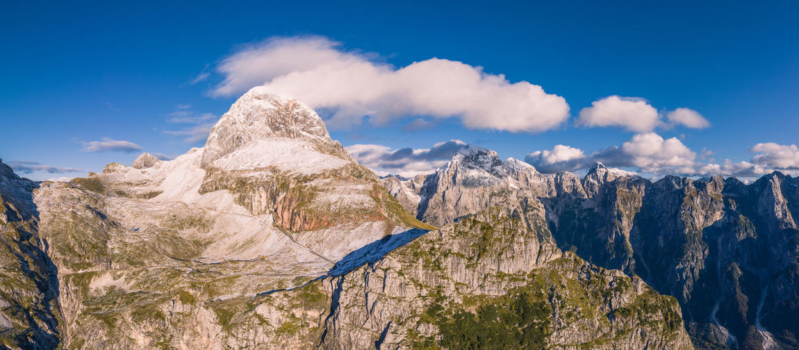 Panoramic view of the mangart mountain range in the julian alps with mountain pass road, slovenia.