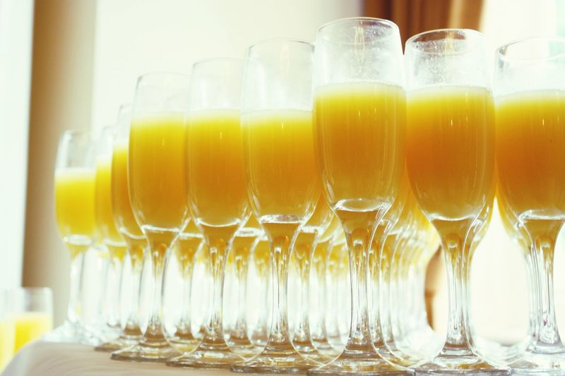 Close-Up Of Orange Juices In Wineglasses On Table