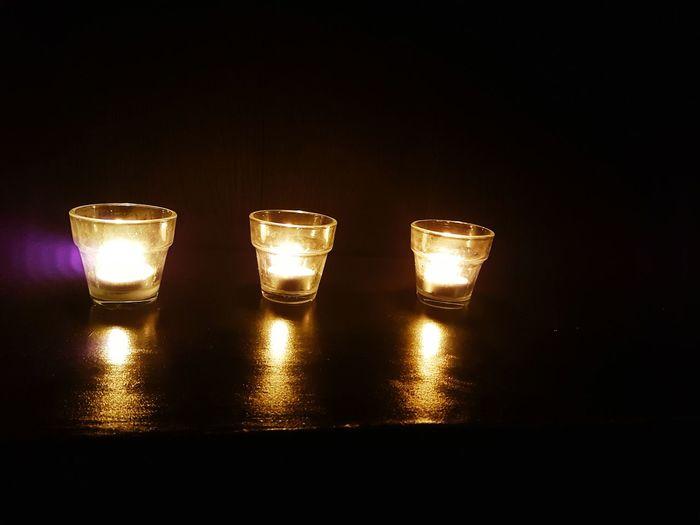 Close-up of illuminated tea light candles against black background