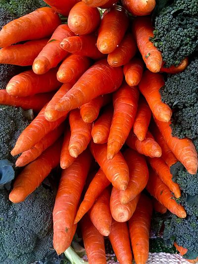 High angle view of carrots by broccoli for sale at market stall