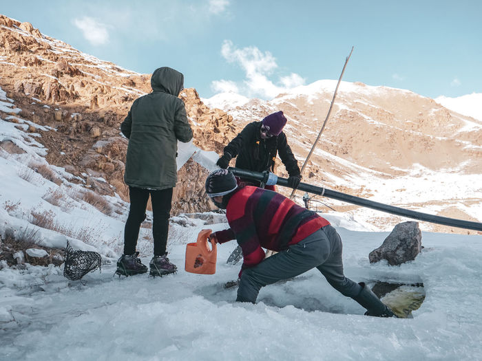 Rear view of people on snowcapped mountain during winter