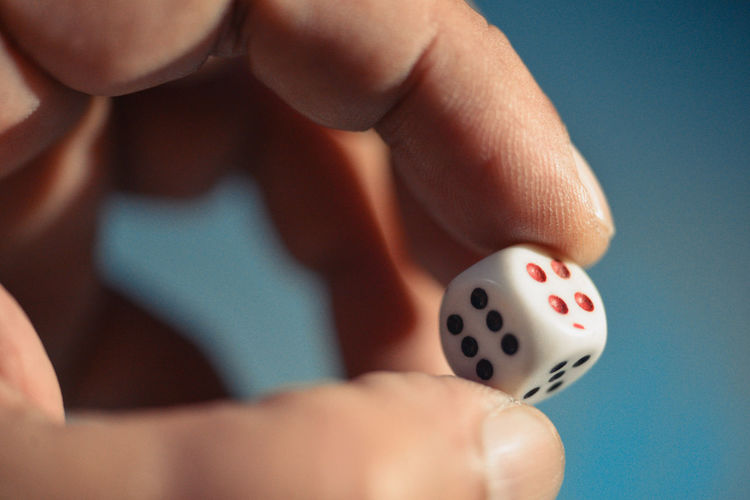 Close-up of person holding a dice at night