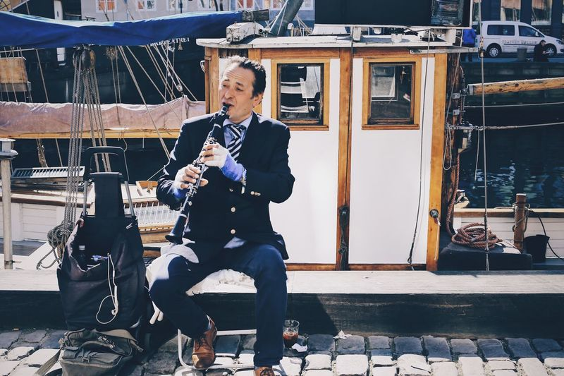 Street musician Clarinetist Clarinet Musical Equipment Musical Instrument Tranquil Scene Harbor Boat Street Life Musician Full Frame People City View  Full Length One Person Lifestyles Real People Leisure Activity Casual Clothing The Art Of Street Photography Men Holding Day Outdoors Footpath Seat Adult Front View