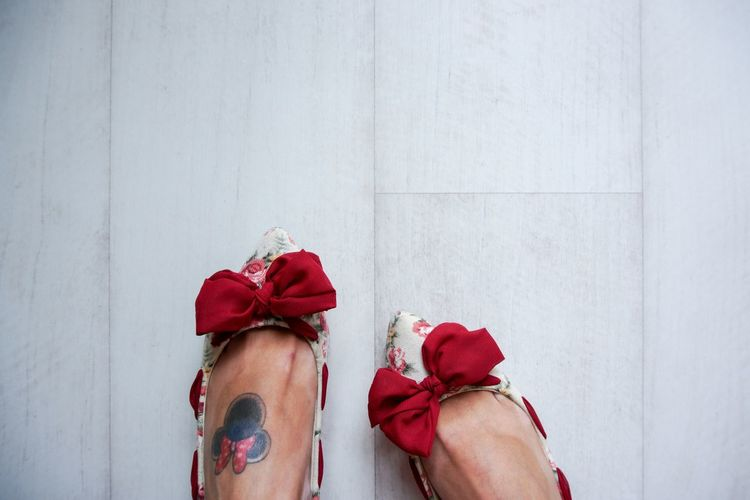 Low section of woman with tattoo wearing red bow shoes