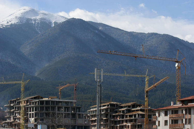 Construction cranes on a mountain in heavy constructions of hotels ruin the nature. Dangerous climate changes. Great pollution of nature. Constructions in protected natural areas, parks. A changes in global or regional climate patterns. Construction Hotels Industrial Machinery Nature Warming Bansko Building Bulgaria Clean Concrete Crane Danger Dangerous Environment Global Healthy Eating Mountain Park Pollution Protected Area Resort Sick Ski Smell