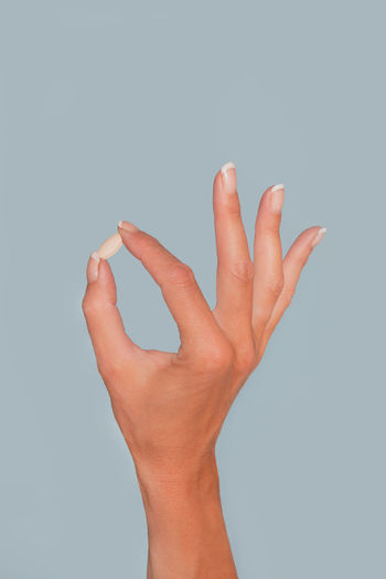 Beautiful female hand holds pill. Isolated on blue background, copy space Pill Health Care Medication Medicine Healthcare And Medicine Health Human Hand Hand Studio Shot Human Body Part One Person Indoors  Human Finger Finger Body Part Copy Space Unrecognizable Person Gesturing Gray Background Close-up Cut Out Gray Personal Perspective Holding Colored Background Human Limb Blue Background Copy Space