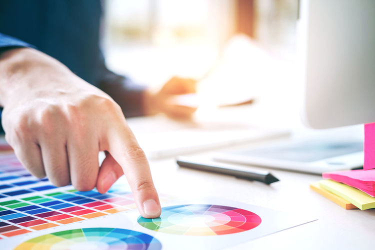 Midsection of graphic designer pointing at color swatch on table