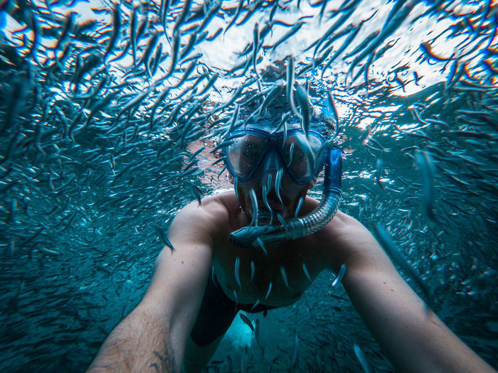 Shirtless man snorkeling amidst fishes in sea