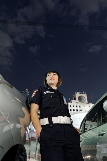 Low angle view of female police officer standing by cars against sky