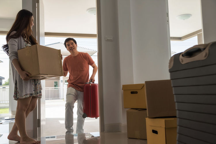 Happy Asian husband carry luggage into new house while female wife carry box and look at her man. moving with many boxes and luggage. First home for new begining couple life. Cardboard Box Moving New York Adult Casual Clothing Couple - Relationship Door Emotion Full Length Indoors  Leisure Activity Lifestyles Luggage Men People Real People Smiling Standing Togetherness Two People Window Women Young Adult Young Women