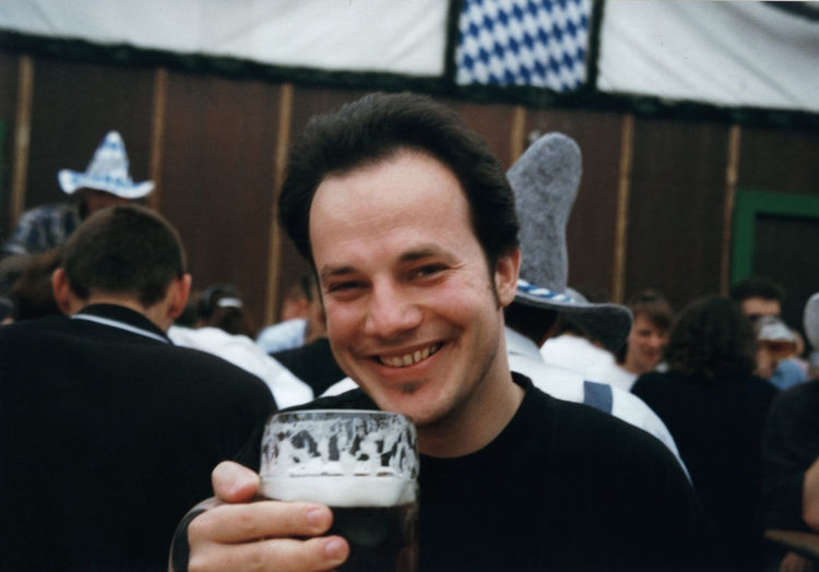 Portrait of man smiling while having beer against people during oktoberfest