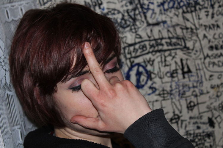 Close-up of woman with eyes closed showing obscene gesture