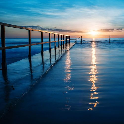 Railing on sea against sky during sunset