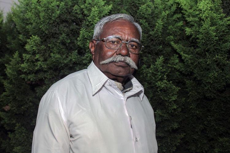Portrait of senior man against plants