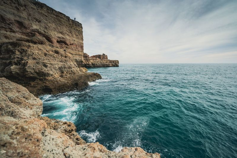Man on the ledge Algarve Portugal Sea Water Sky Beauty In Nature Beach Scenics - Nature Rock Nature Tranquility Tranquil Scene Horizon Over Water Land Day Rock - Object Cloud - Sky Solid No People Horizon Outdoors