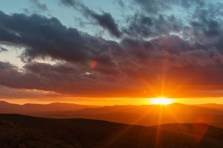 Sky Sunset Cloud - Sky Beauty In Nature Scenics - Nature Sun Orange Color Tranquility Tranquil Scene Mountain Sunbeam Landscape Environment Sunlight Nature Idyllic Dramatic Sky Non-urban Scene No People Mountain Range Lens Flare Outdoors Bright