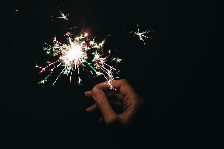 Cropped Image Of Woman Holding Sparkler Against Black Background