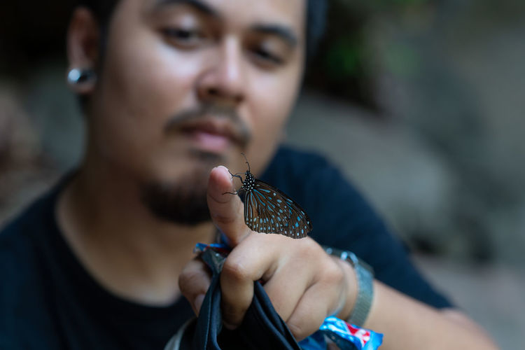 Close-up of man holding butterfly