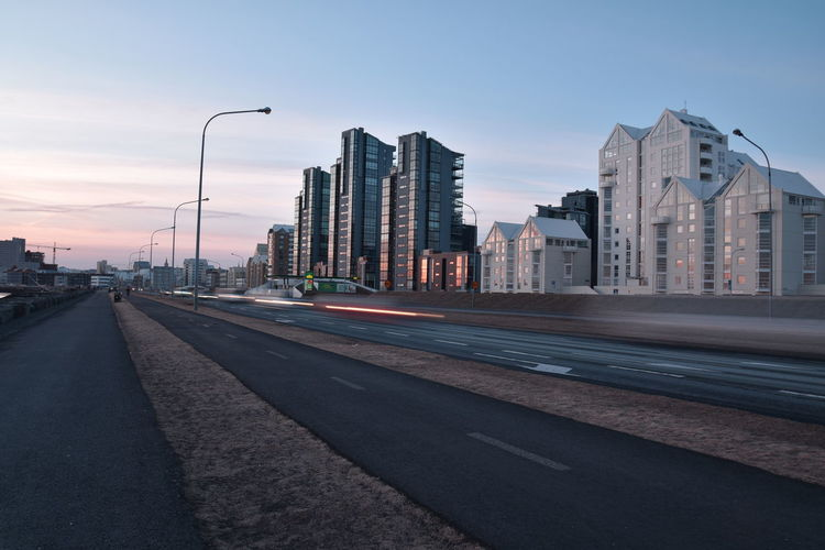 Road by buildings against sky during sunset in city