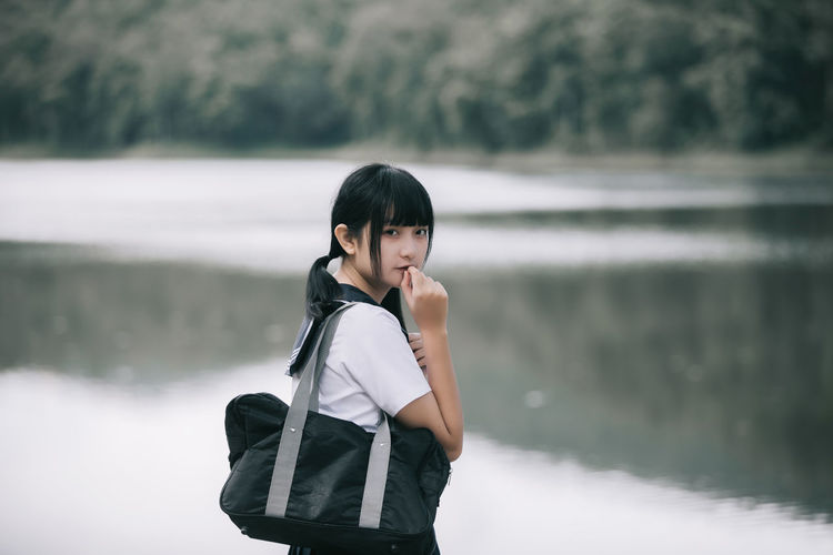 Portrait of young woman standing by lake