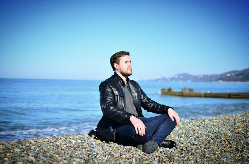 Full length of man sitting on pebbles against sky