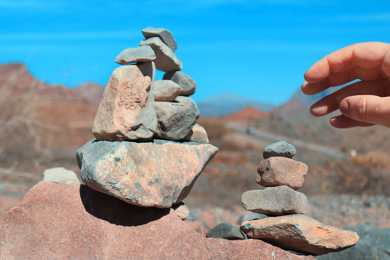 Close-up of hand holding stack of rocks