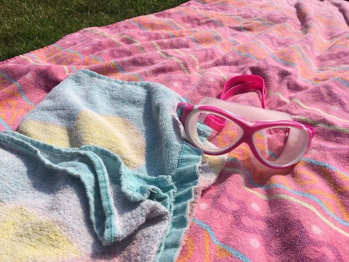 A Day At The Swimming Pool Towels Goggles Textile Multi Colored High Angle View No People Still Life Close-up Pink Color Pattern Day Blanket Indoors  Fashion Textured  Backgrounds Full Frame Towel Clothing Nature Floral Pattern Personal Accessory