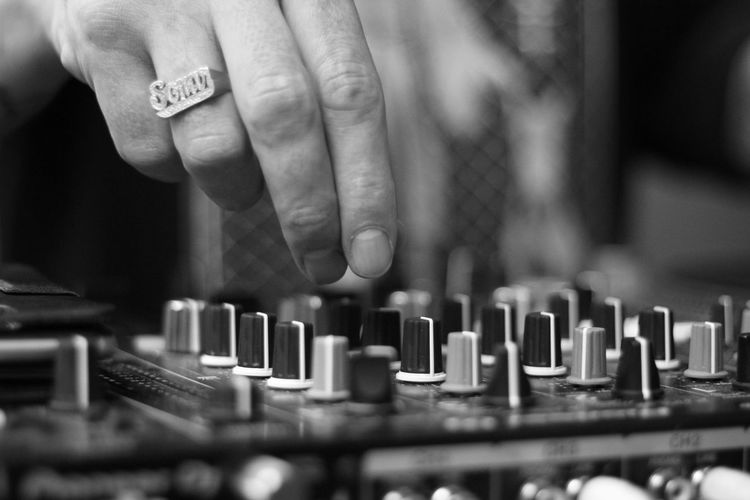 Cropped hand of person operating sound mixer
