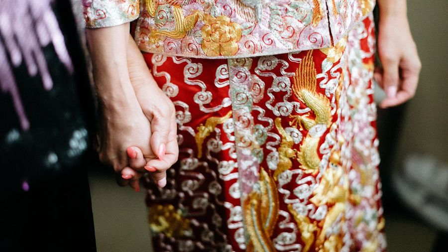 Midsection of women wearing traditional clothes while holding hands